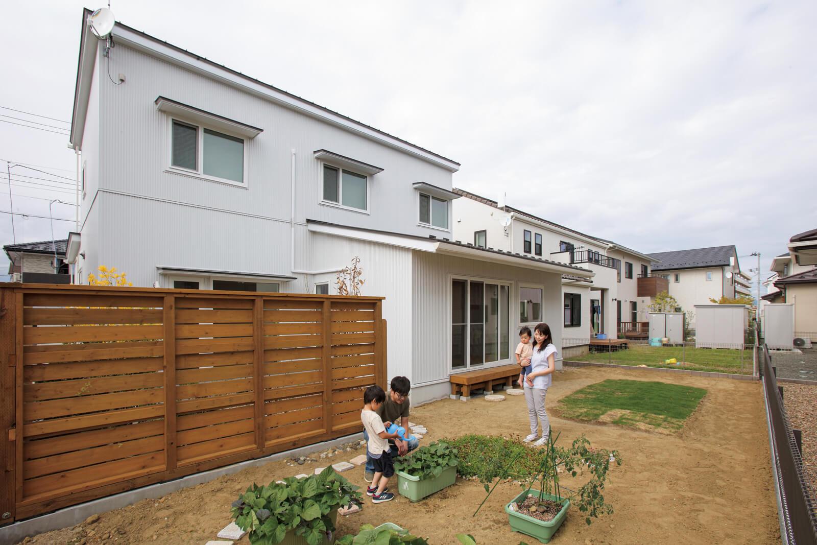 南側から建物を望む。外からの視線を遮るルーバーを設置し、内側に植栽を配置している。現在進行形の庭づくりも家族の楽しいひととき