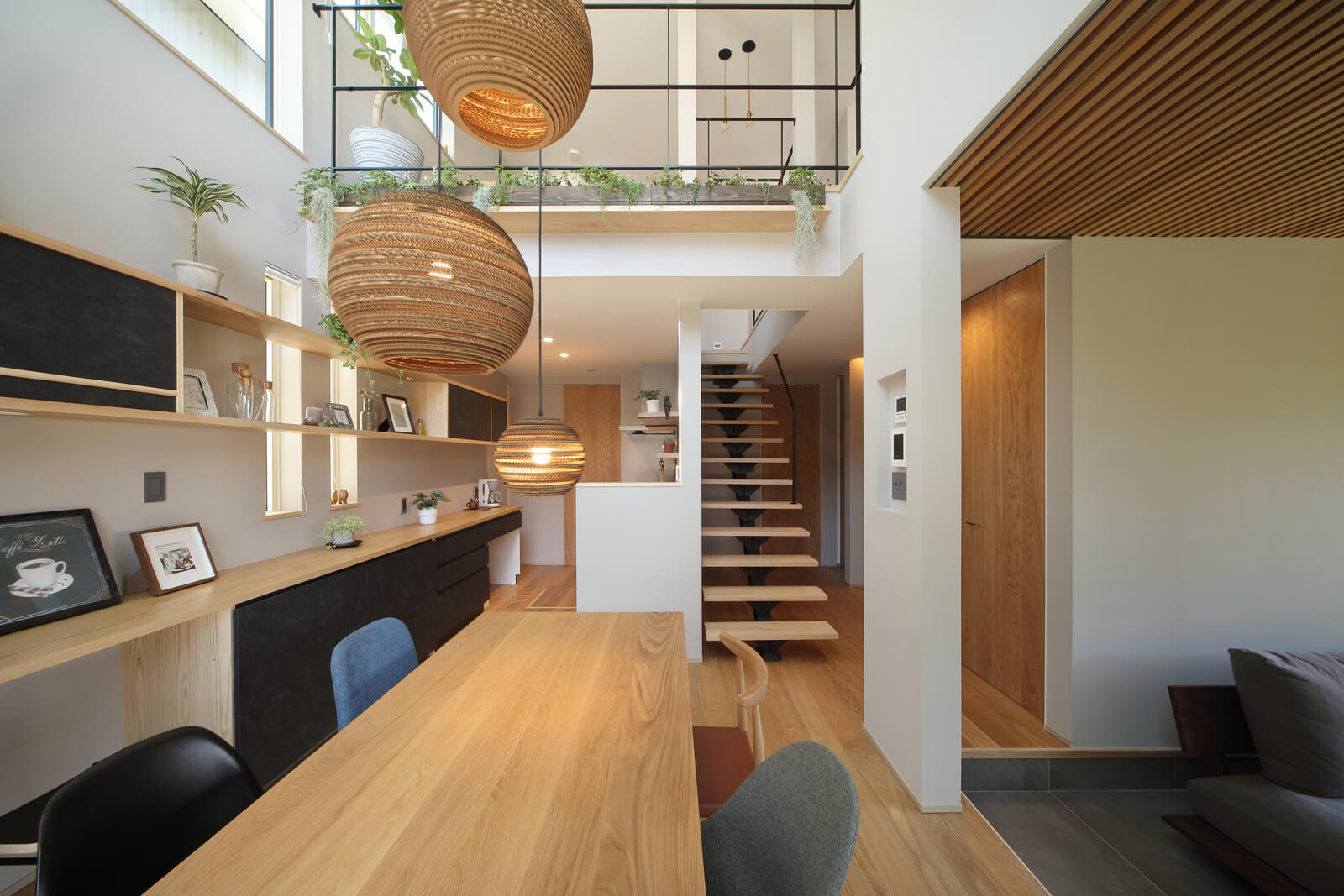 一本力桁の階段を中心に回遊できる造り。キッチンからダイニングまで一体でつくり上げられた壁面収納は子どもの勉強スペースにも最適