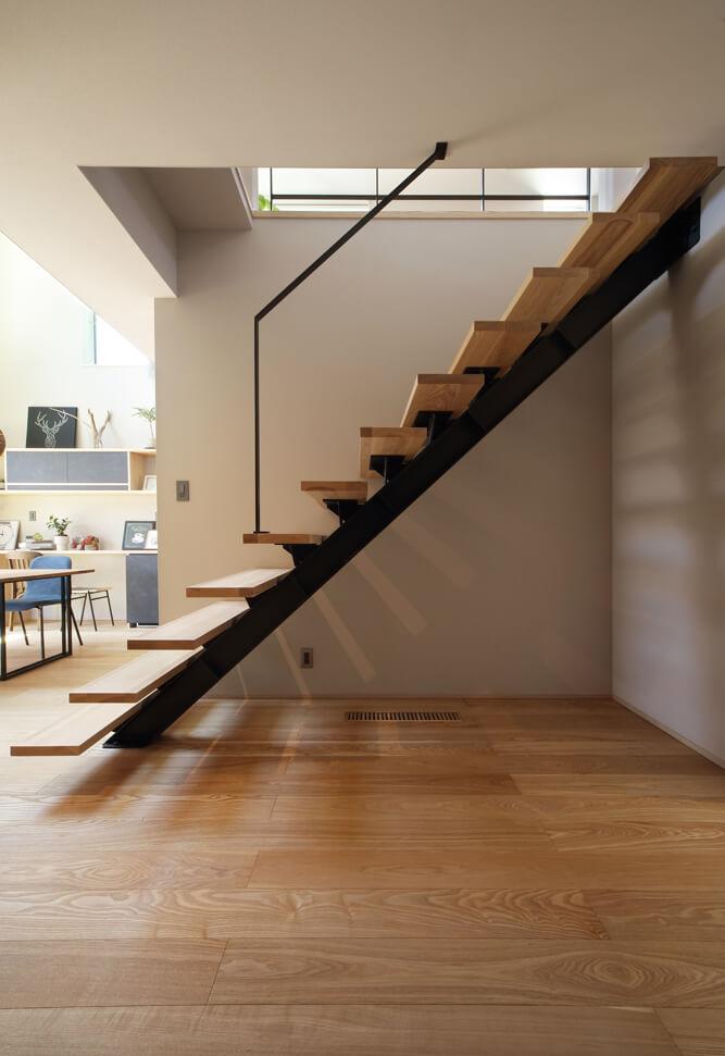 浮遊感のある階段が美しい。エアコンからの冷暖気は基礎空間を経由し、階段下など随所に設けられた床ガラリから吹き出される
