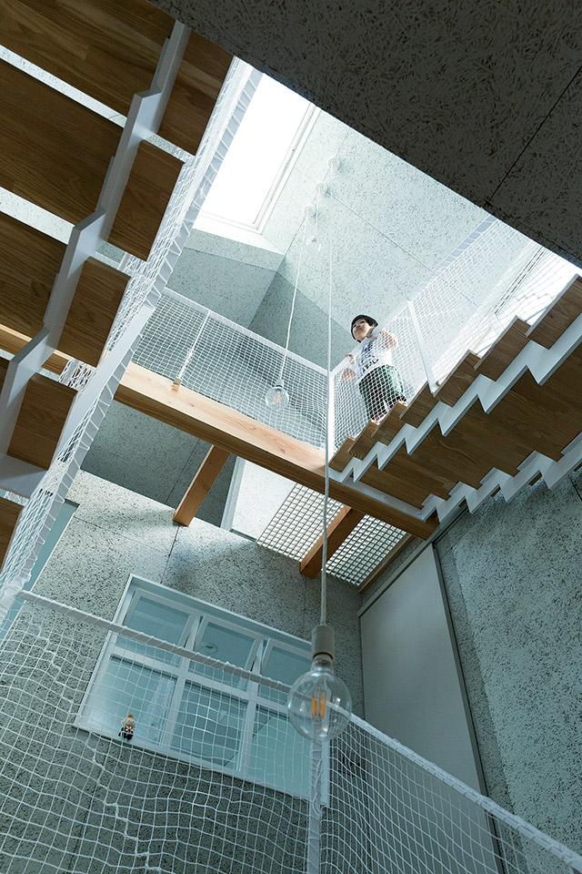 吹き抜けの階段を見上げる。ロフト階のテラスから降り注ぐ光が心地よい