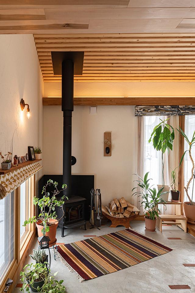 広い玄関土間の一角に置かれたヨツールの薪ストーブ。インテリアグリーンやラグ、照明が心地よさを演出