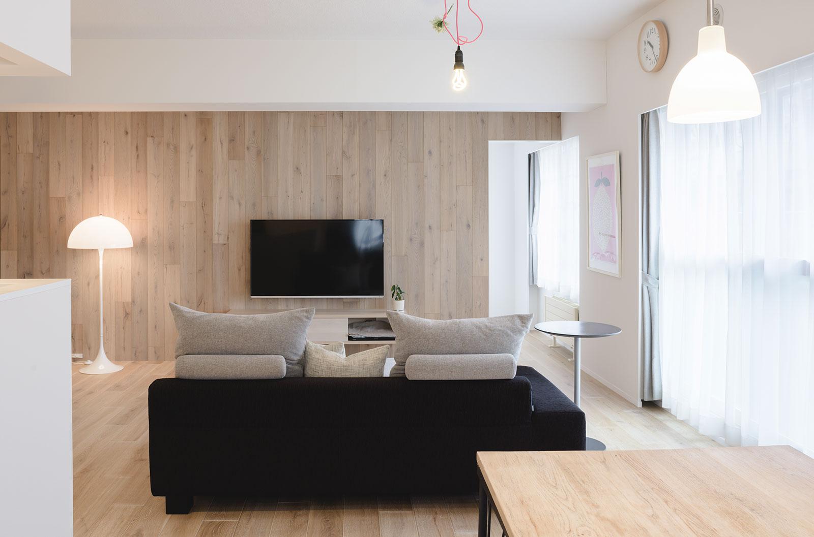 白染色の床とアクセントウォールのおかげで、マンションでありながらも、木の心地よさが伝わる室内