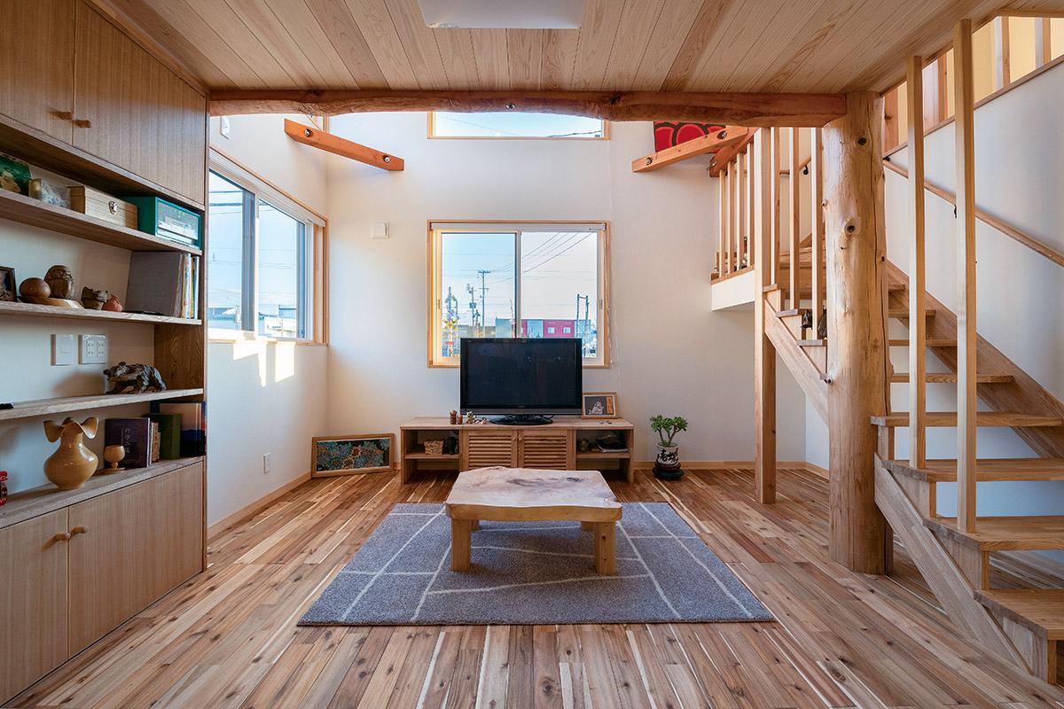 さまざまな木の色合いや特性を生かしてつくり上げられたリビング。トチの一枚板を使ったテーブルがアクセントに。暖房はテレビ台の下に設置されたFF式床下暖房機がメイン。通気口から出る温風で全館をふんわりと暖める