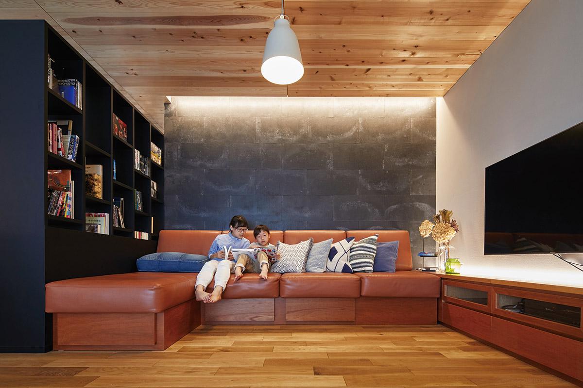2階リビング。ソファ背面の壁にあしらわれた表情豊かな板材が、上質感の中にインダストリアルな趣を添える