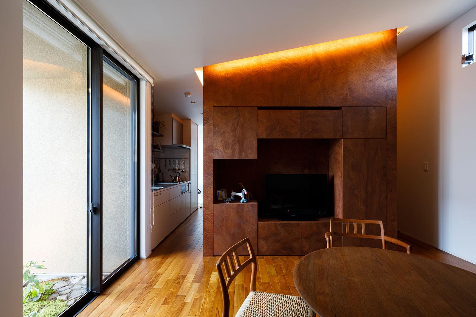 フローリングの延長のような、造作のテレビ台兼収納壁面が天井まで伸びている。裏手はトイレや洗面などがあるパウダールーム