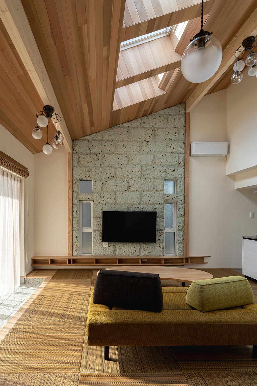 大谷石の壁と柄入りのモダンな琉球畳が調和する吹き抜けのリビング