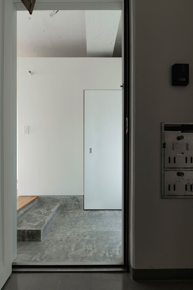 自然光が届く明るい玄関はモルタル風の仕上げに。年月を感じさせる玄関扉とのコントラストが美しい
