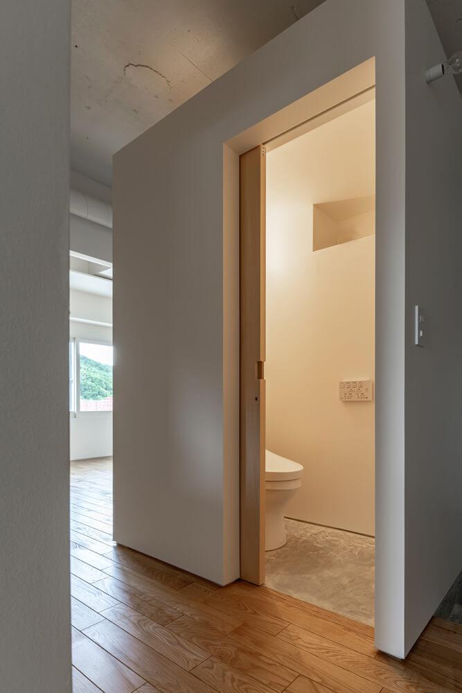 角度をつけると白い箱型にも見えるトイレ。マンションの中であることを忘れる光景のひとつ