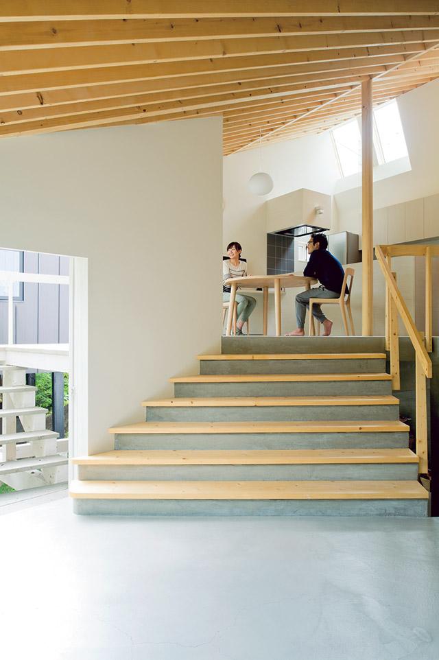 リビングとダイニングをつなぐ幅の広い階段は、時に椅子になったり、遊び場になったり。左にはリビングとダイニング両方から使えるデッキが