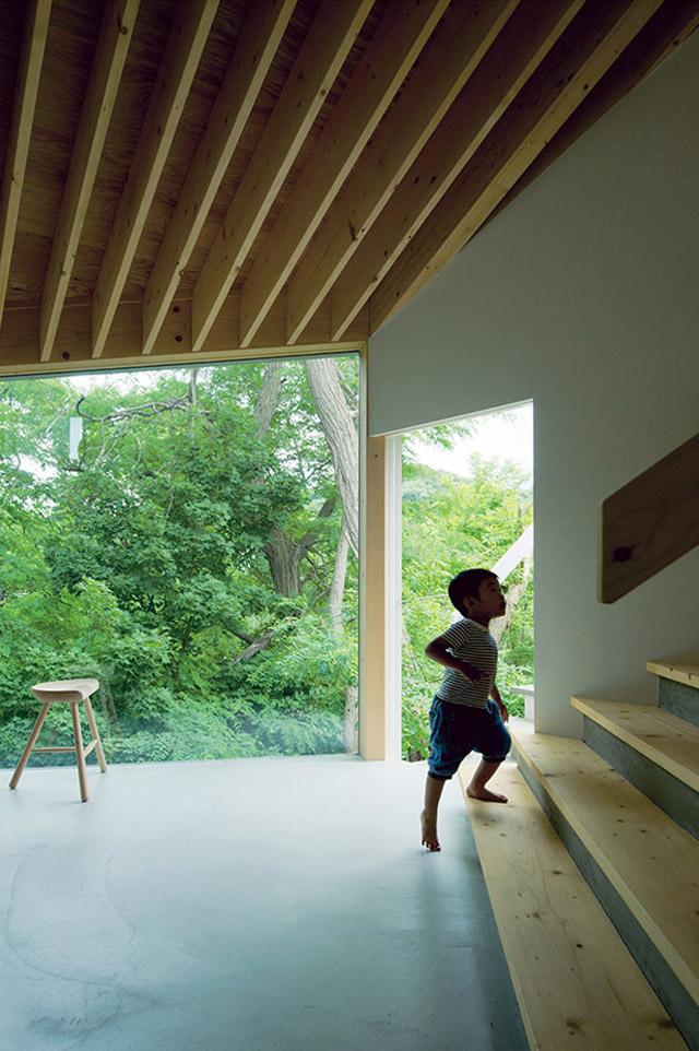 窓枠のない大きな窓が、外の森の景色を美しく切り取る
