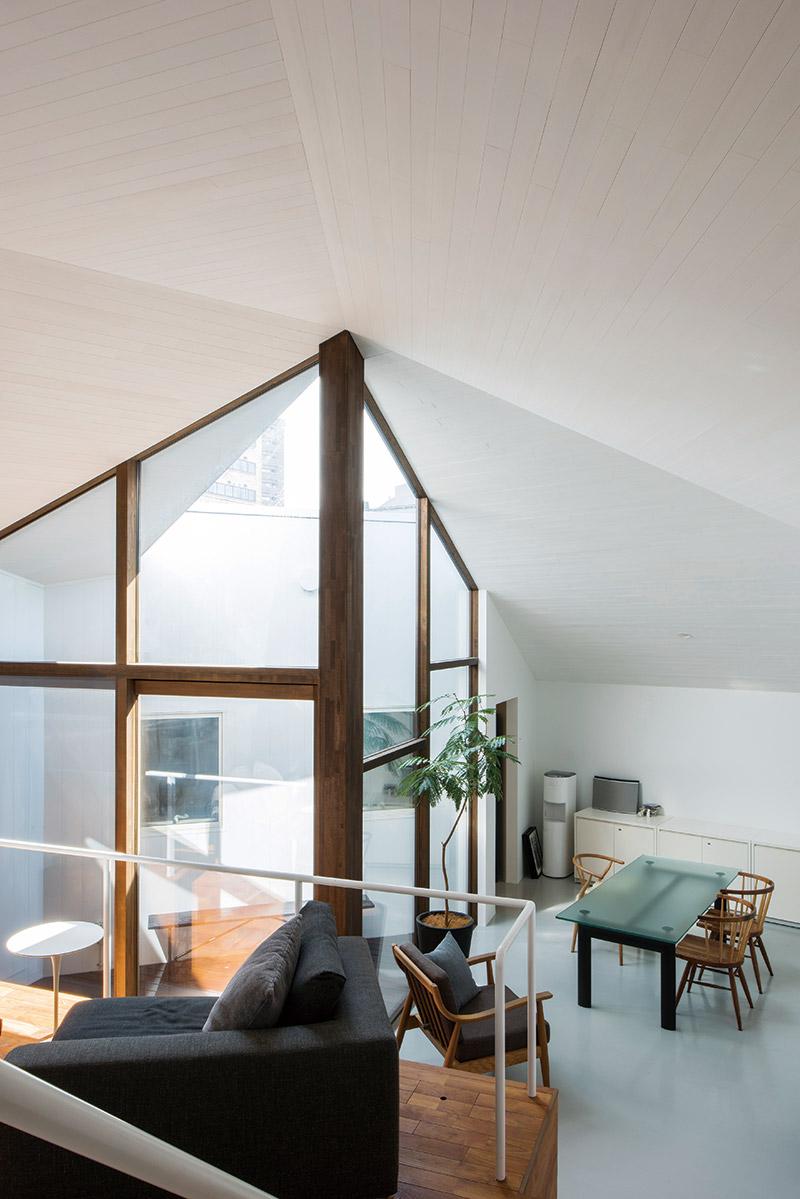 ひな壇状に高低差のあるリビング。中央の光庭から入る光が天井の高い室内を満たす