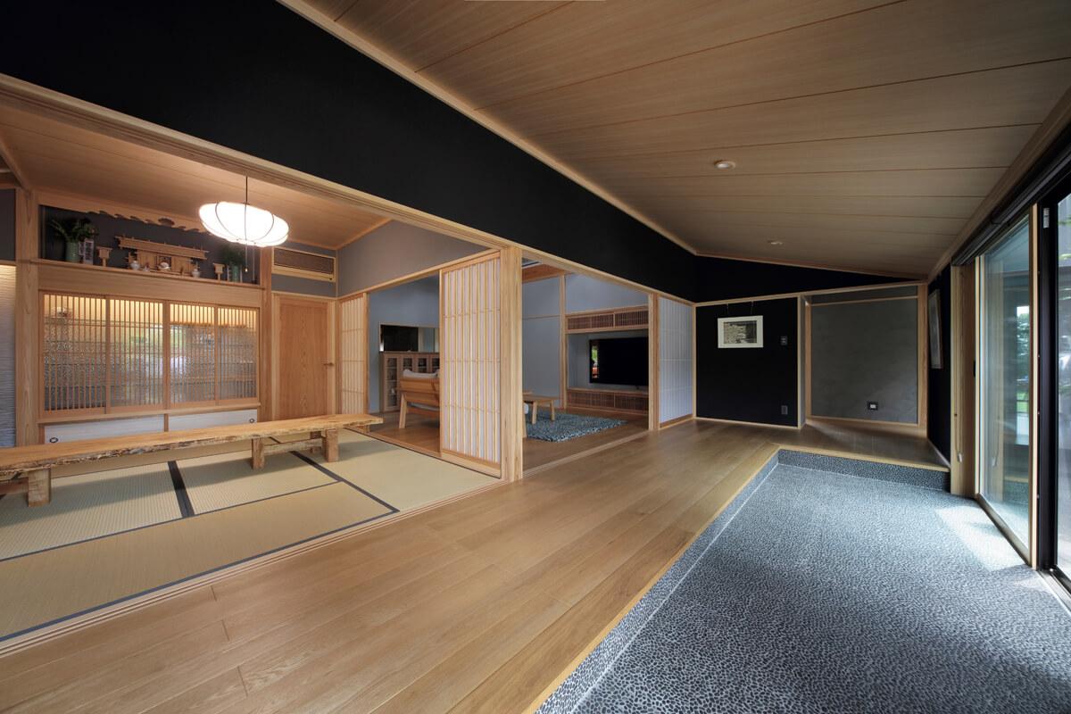 和室とリビング、廊下までが一続きの広い玄関。伝統的な意匠に壁の黒色がモダンな印象を添える
