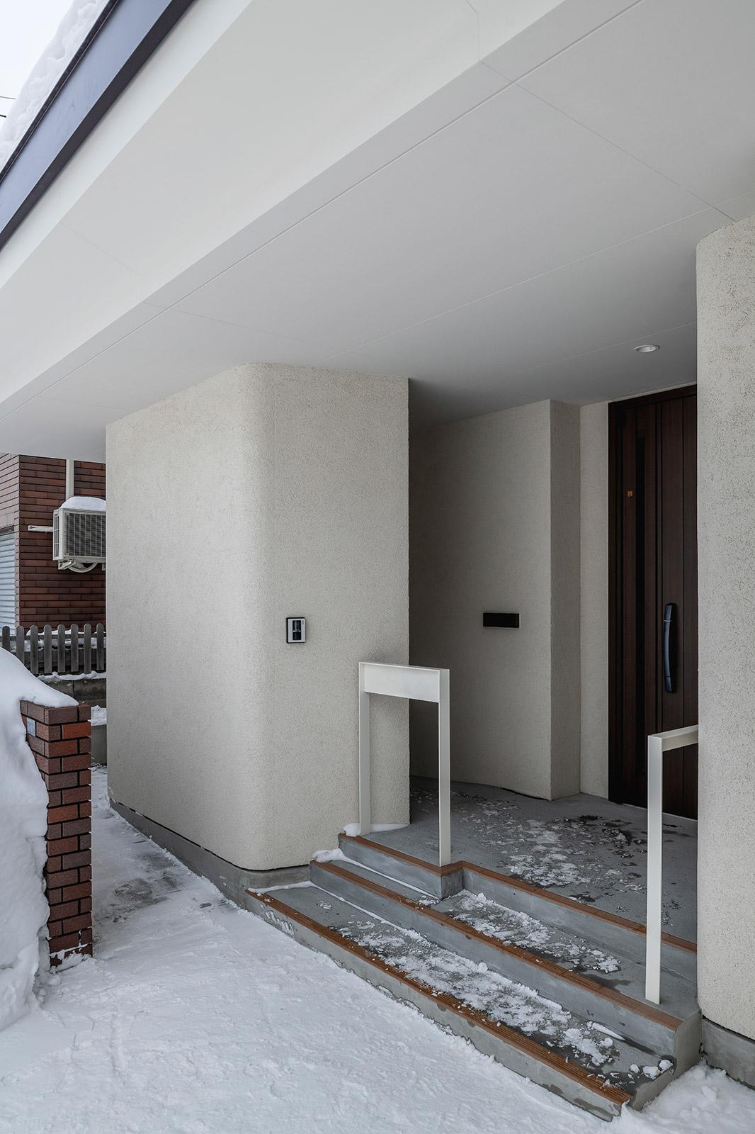 玄関アプローチは段差を低く抑えた階段と、車いす用のスロープを併設したMさん宅