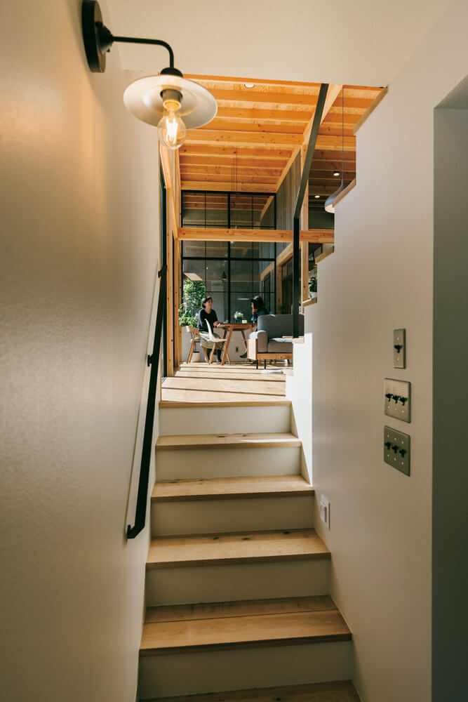 玄関から上がる階段は閉じた印象。だからこそLDKへ足を踏み入れた瞬間の開放感は格別
