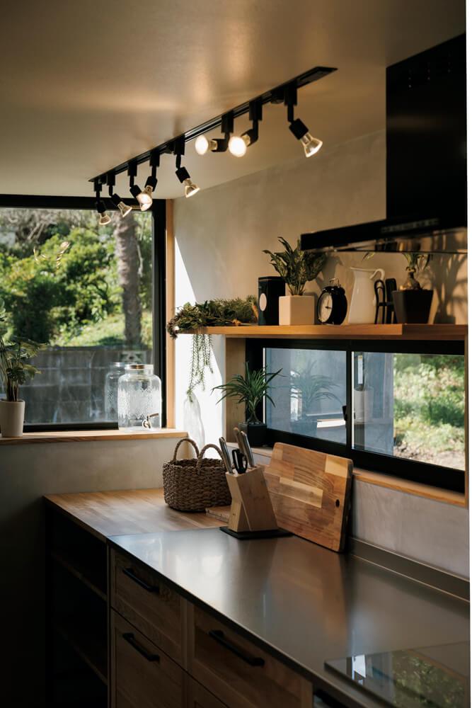 キッチンにディスプレイを兼ねた棚を造作。黒の窓枠とライトが空間を引き締める