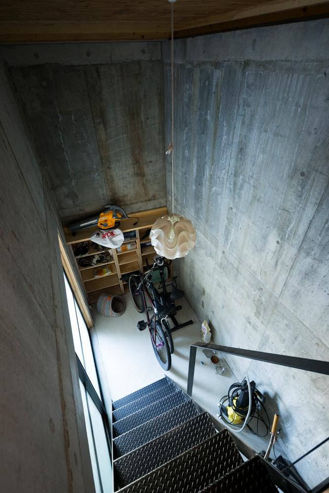 地下のガレージに隣接するコンクリート造の階段室は、物置や愛猫の居場所として使われている