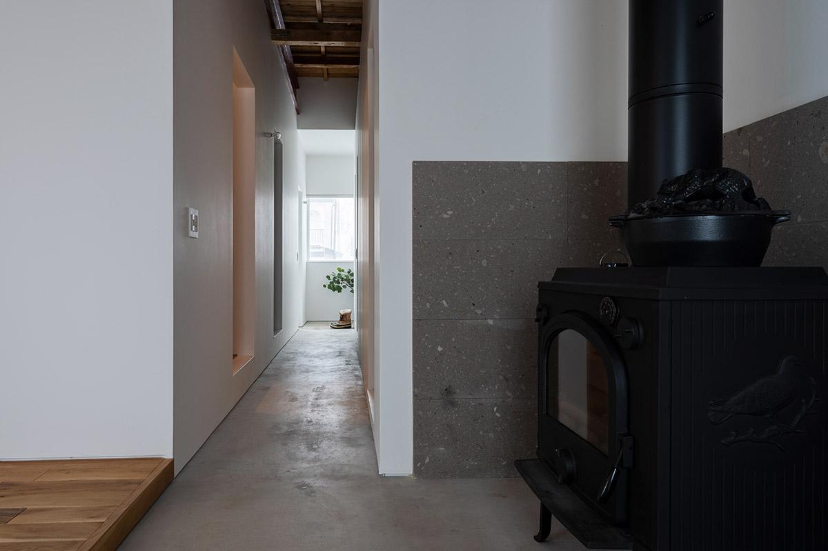 裏手の階段に置かれた薪をストーブまで運ぶ動線は、土間廊下でつながっている。「薪ストーブのある暮らしは八雲町に引っ越してからやってみたかったことです。毎朝、誰よりも早く起きて、薪をくべています」とKさん