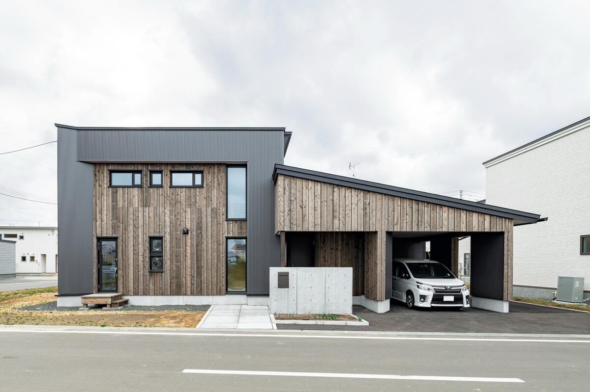 カーポートも一体化させた実用的な設計のお住まい。道南スギの外壁材の風合いが目を引く