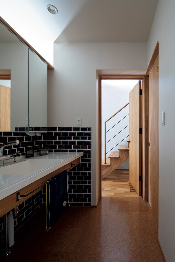 階段脇の扉を開けると、壁の下半分をタイルで仕上げた造作の洗面台