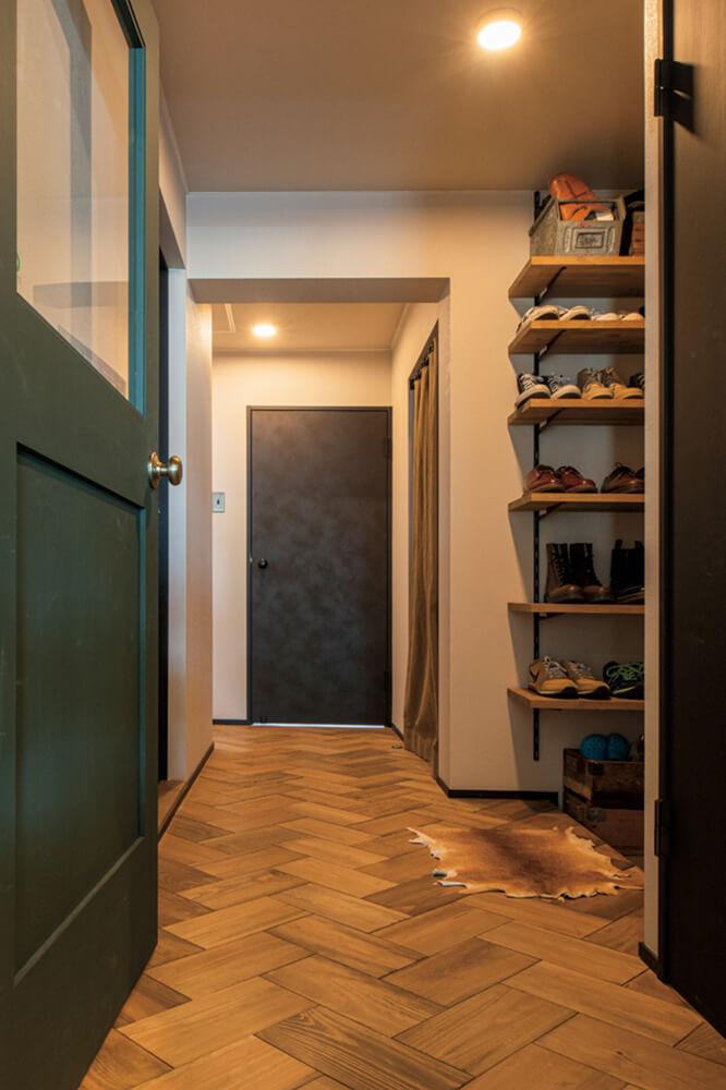 玄関まわりの床は、マツ材のヘリンボーン・フローリングにアップグレード。手前のLDKにつながるドアは、閉めても向こう側の気配を感じられるようにガラス入りをセレクトした