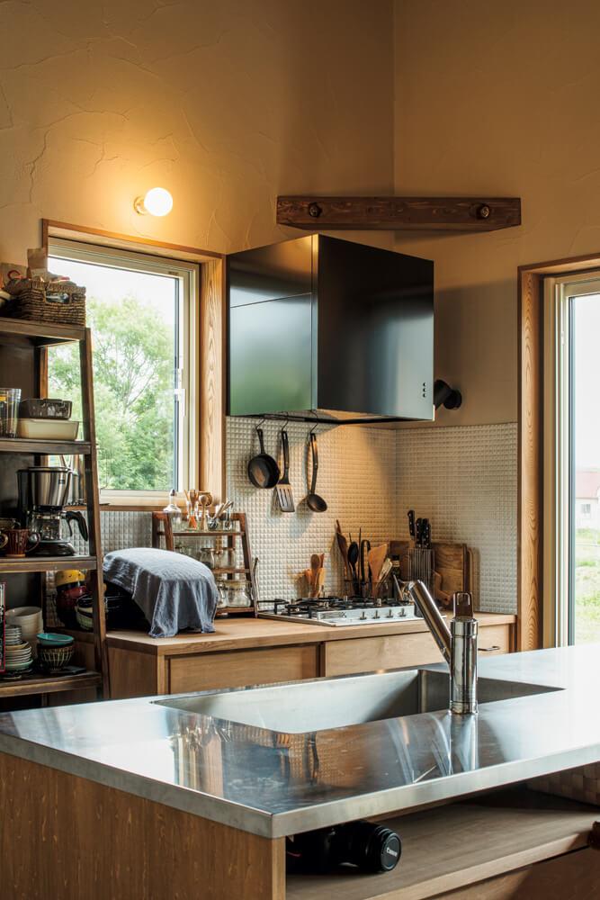 造作した対面式キッチン。ガスレンジを壁付けにすることで、シンクのある作業スペースが広くすっきりする。レンジまわりの壁の白いモザイクタイルが、インテリアのアクセントに