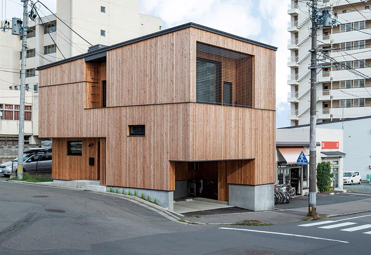 街なかの狭小地ゆえ、駐車場や玄関ポーチ、バルコニー等の屋外機能空間は、緩勾配の屋根を載せた直方体からそれぞれ引き算することで外観を構成
