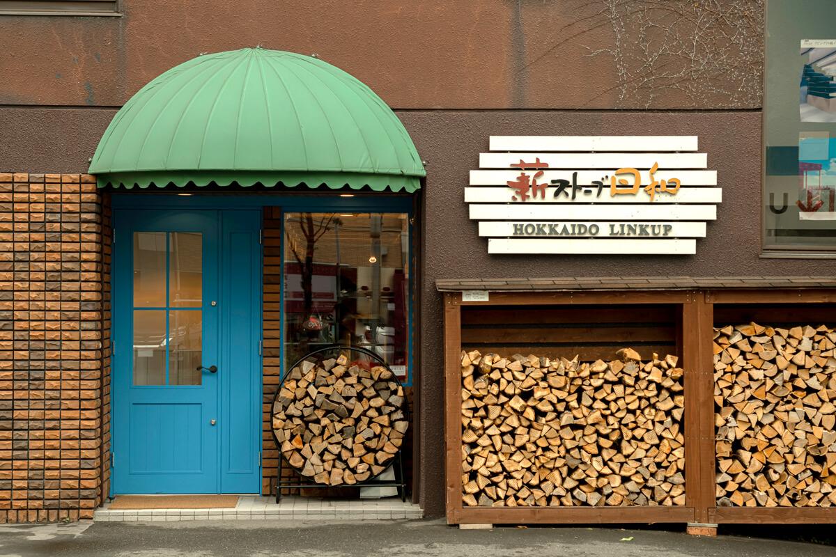 ショールームは木製の薪棚と看板、青い扉が目印