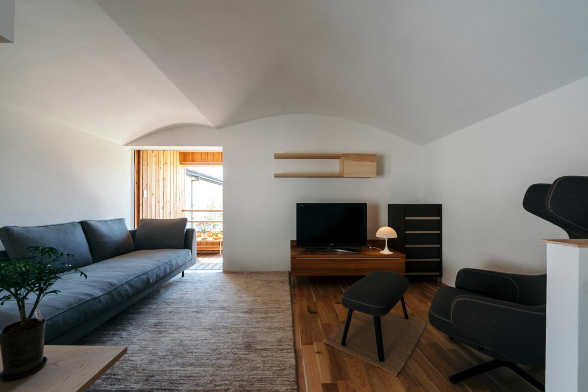 家族をかばい守るようなアール天井。照明も換気扇もなくすっきりと。白壁とリネンのソファの組み合わせが美しい
