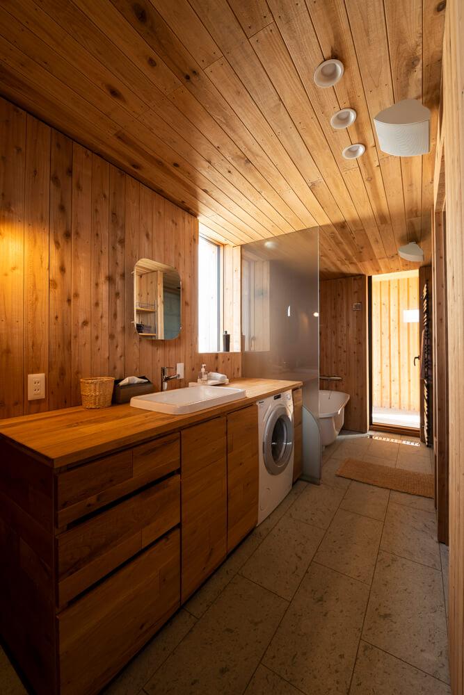 2階の水まわり。床材の十和田石は県内比内町で産出される。秋田スギの板材を荒めに加工した壁のテクスチャが個性的