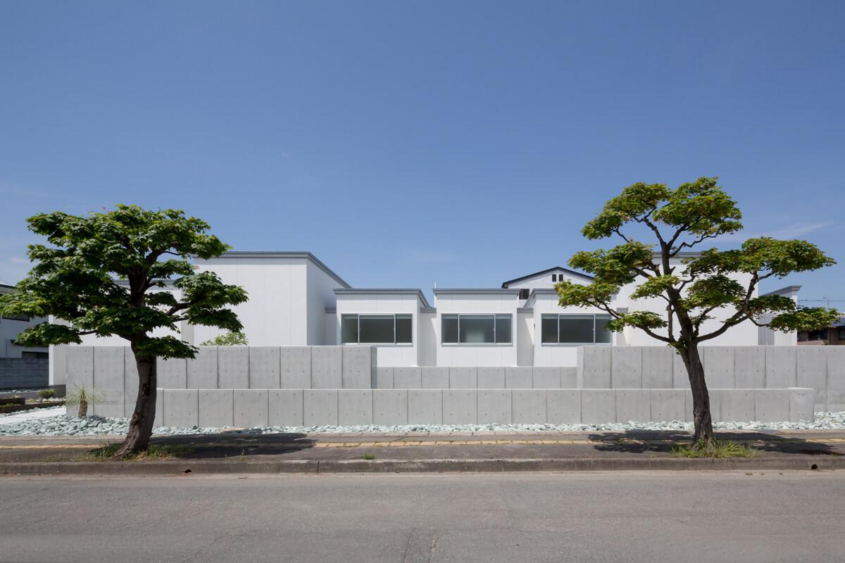建物全体を高い塀で囲うのではなく、コンクリート造の塀をバランス良く配置。街に開かれた住まいとした