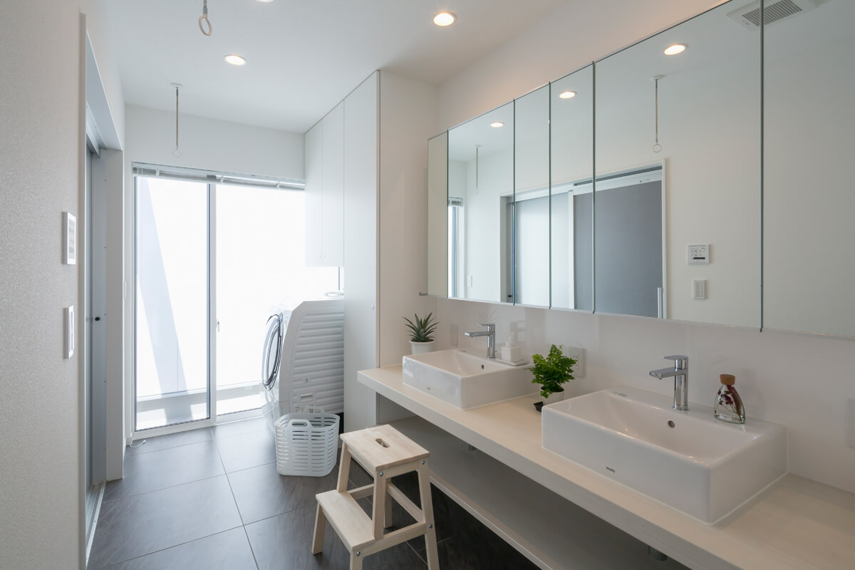 清潔感のある明るい洗面まわりは、室内干しができる仕様に。ご家族の身支度の時間が重なることを想定して、洗面台はツインボウルとした。収納付ミラーは三面鏡にもなって化粧品などが収納できる