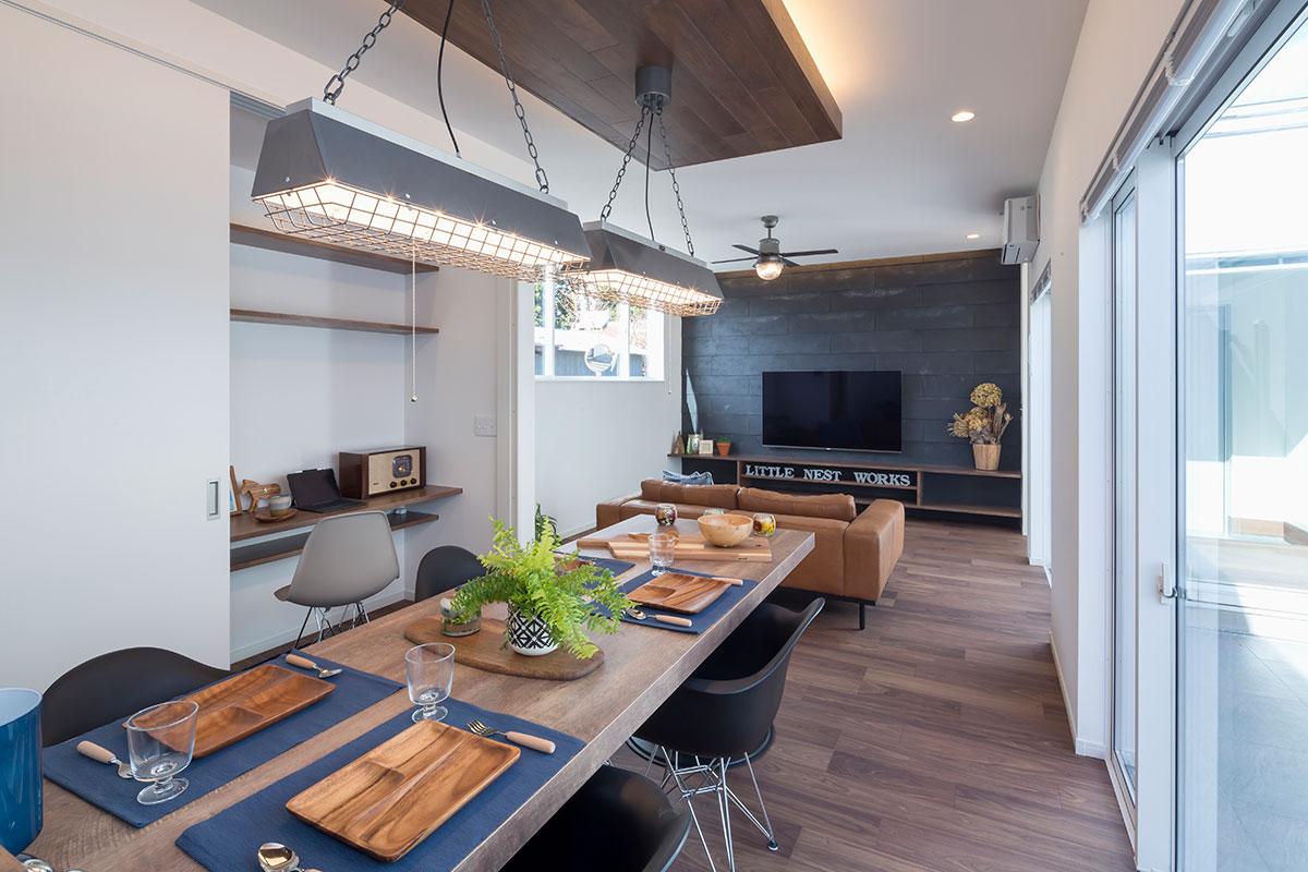 木製のテレビボードの壁面には、ダークグレーのタイル素材をバランスよく配置