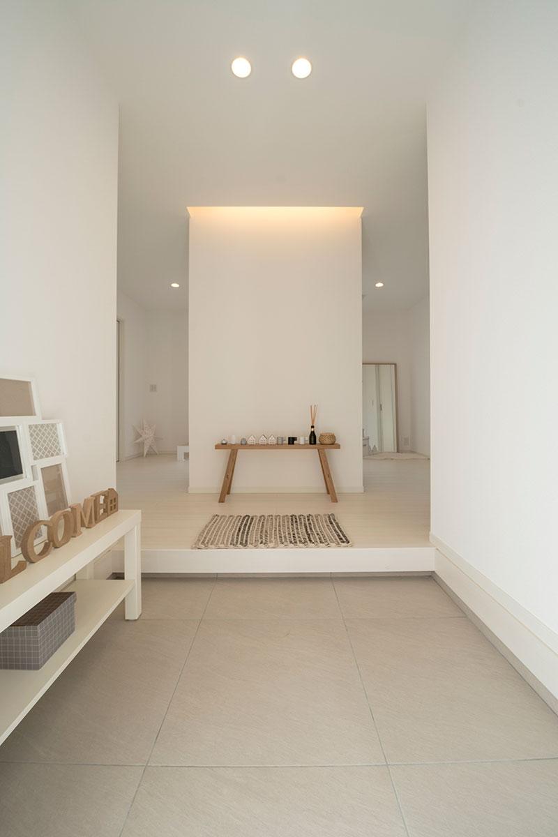 間接照明が照らす白い壁が印象的な玄関。1階は中央にトイレ、その左右に夫婦の寝室は配したユニークな空間構成となっている