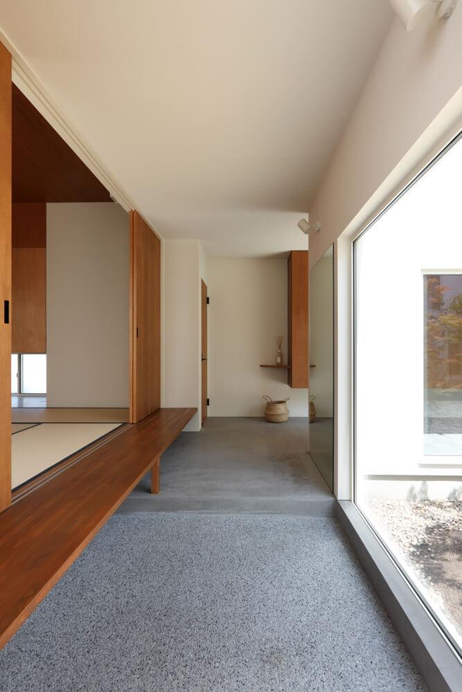 玄関と小上がりの和室。段差を利用したベンチに腰かけて靴を履いたり、庭を眺めることができる