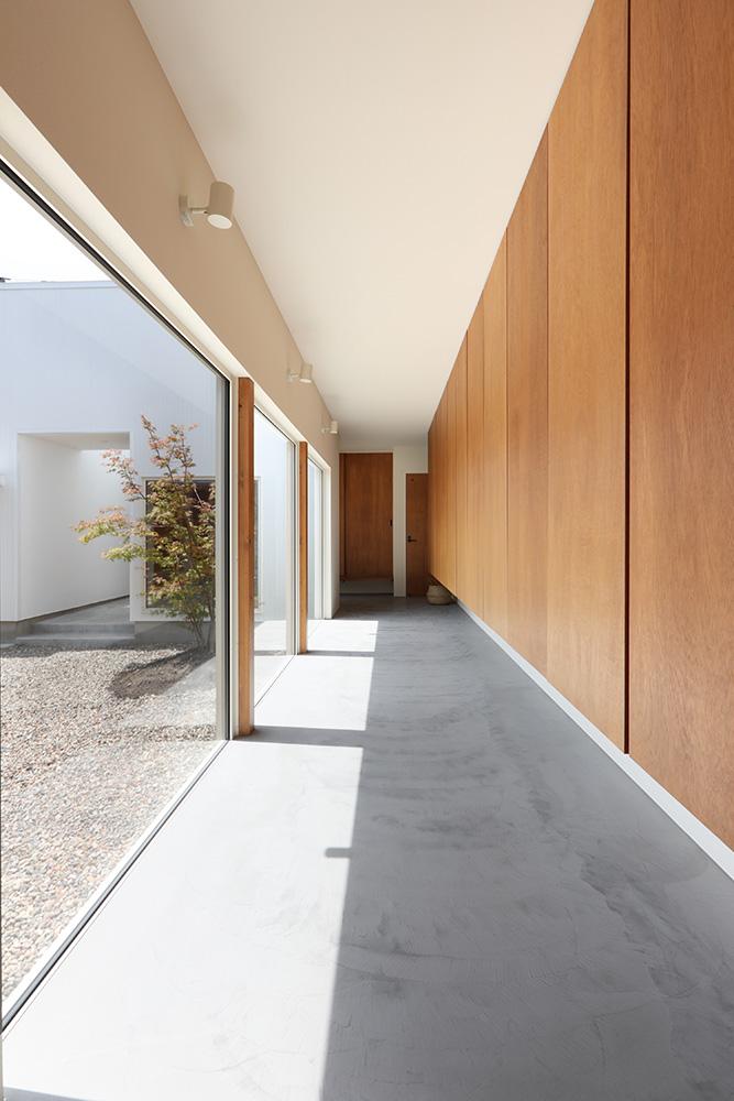 玄関とLDKを結ぶ長い廊下。小さなテーブル、椅子などの家具が置けるようゆったりとした幅を持たせている
