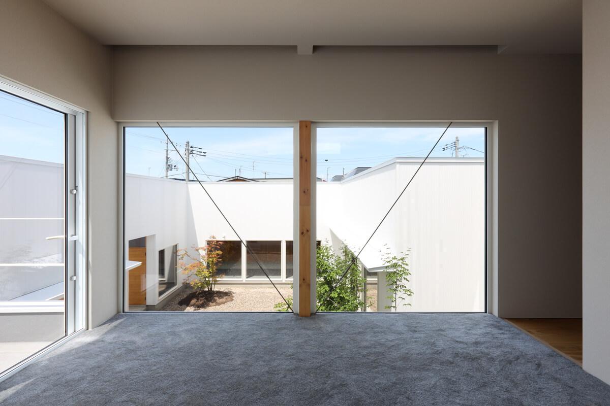 床からの大きな開口部とフワフワしたカーペットの感触で浮遊感を感じる2階寝室。左手は庭を一望できるルーフバルコニー