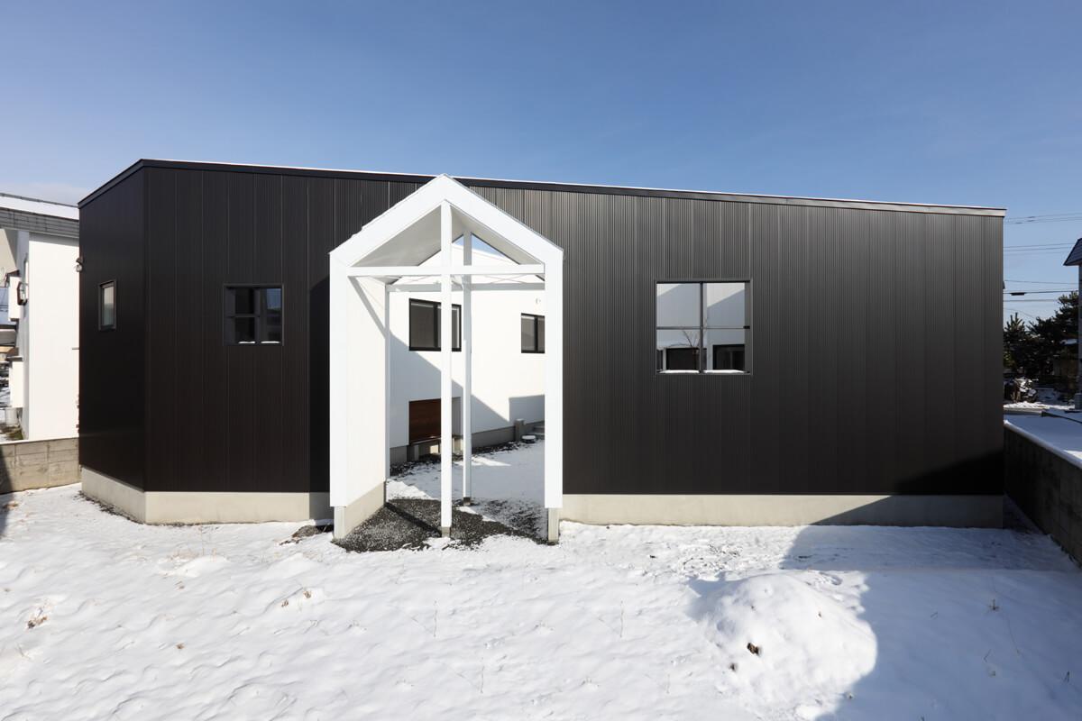 建物に囲まれた「内庭」と外部の「外庭」、2つの庭を持つ住宅。十字のゲートがそれぞれをつなぐ