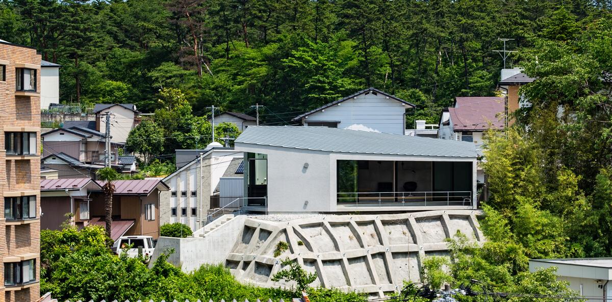 コンクリートの擁壁が既存の状態であり、この土木的なマテリアルを住宅のファサードに取り込み、背景の森林公園の自然や環境と一体になるような住宅とした