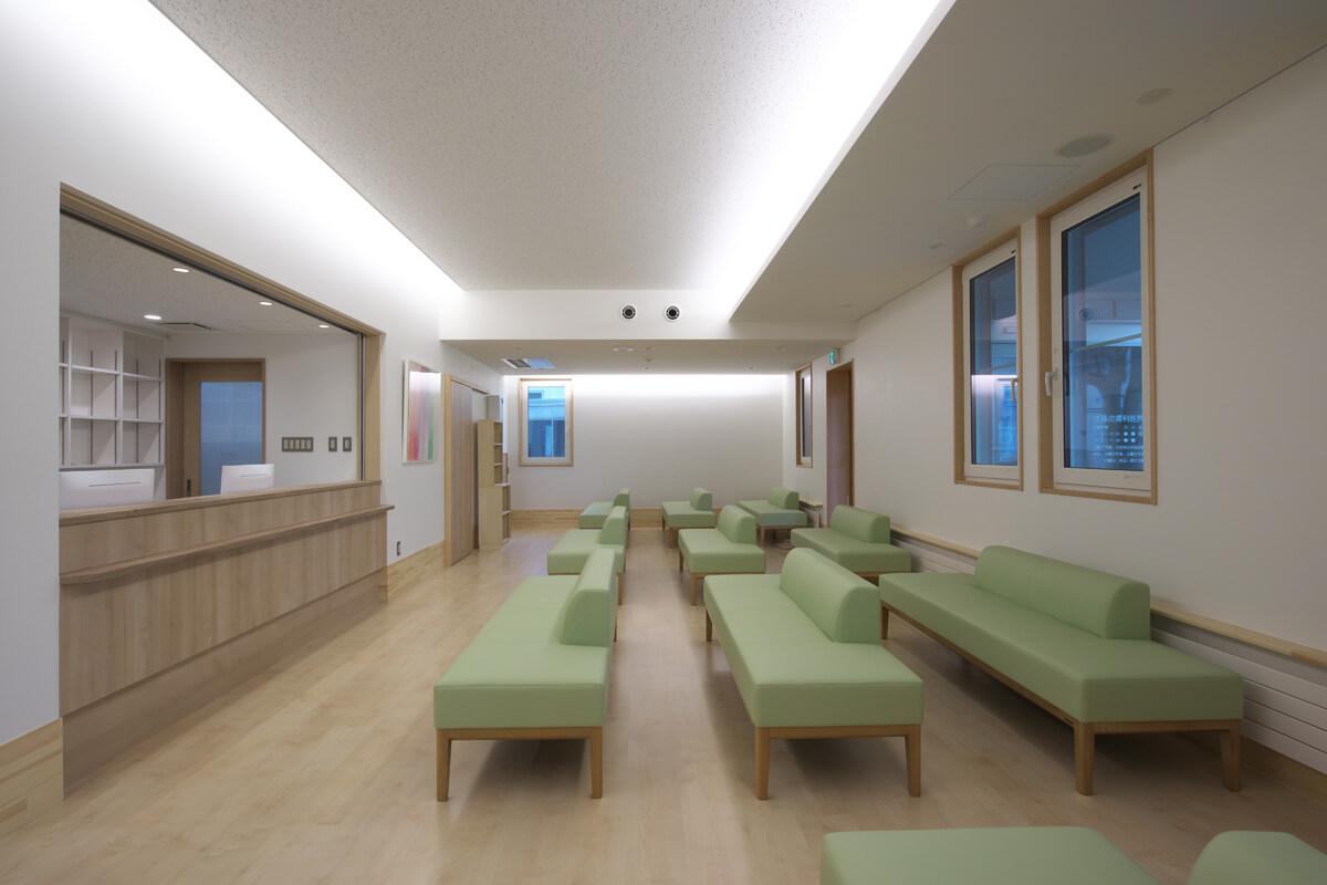 待合室。左手に受付、右手外がポーチ。照明は間接照明主体としてシンプルで柔らかい雰囲気とした