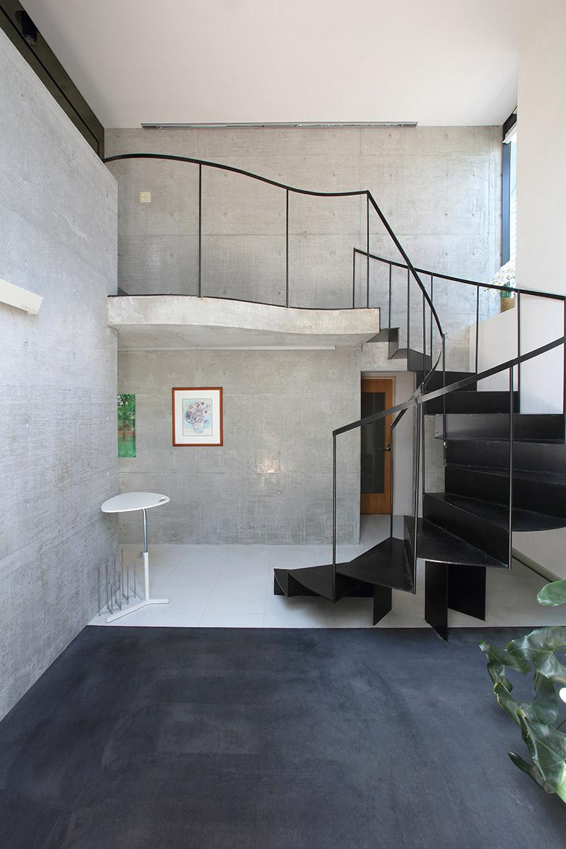 事務所エントランス内。吹き抜けの大空間に螺旋階段を配した大らかでクールなデザインが、訪れる人を出迎える