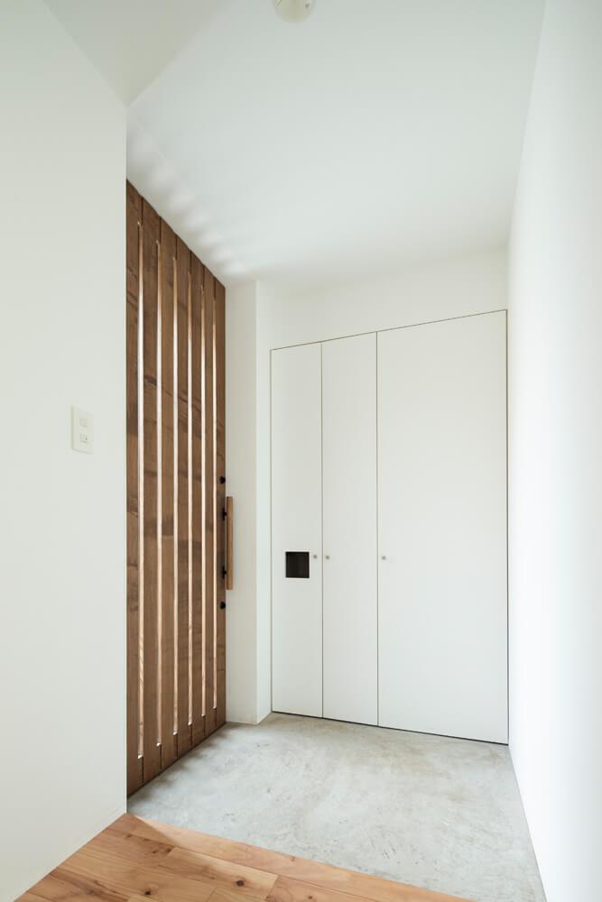 スリットになっているドアからの採光で明るい玄関