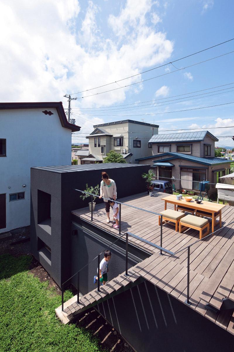 大小の箱を並べた2階建ての住宅。地面から持ち上げられたルーフテラスは周囲と適度な距離感のあるプライベート空間