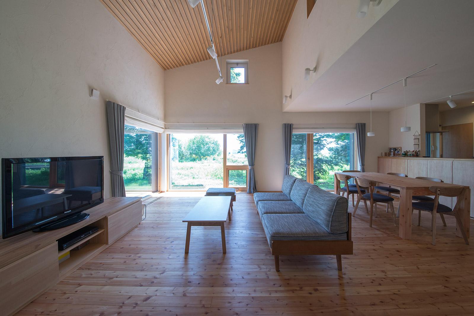 天井、壁、床に自然素材を使ったLDKは、家族みんなが集う空間。吹き抜けや外の風景を取り込む大きな窓のおかげで開放的