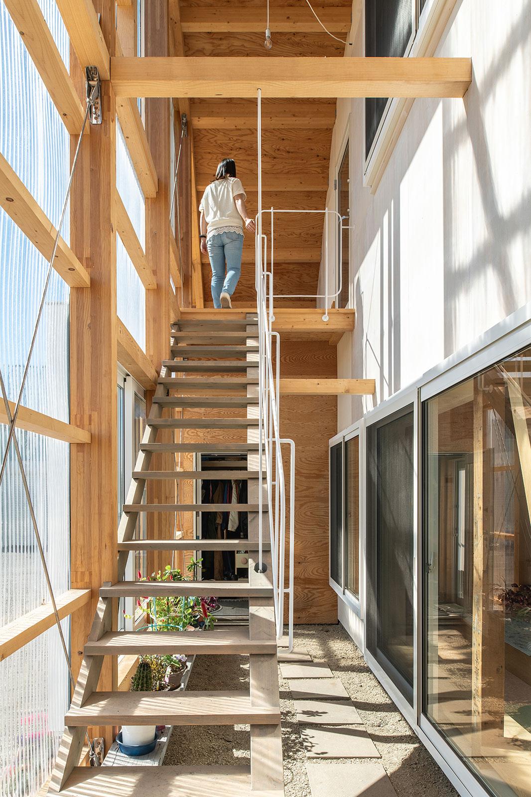 増築された半屋外空間は風除室、テラス、アクセス空間、農家玄関を兼ねる多目的空間。風除室から延びる階段を上ると、子世帯の生活エリア