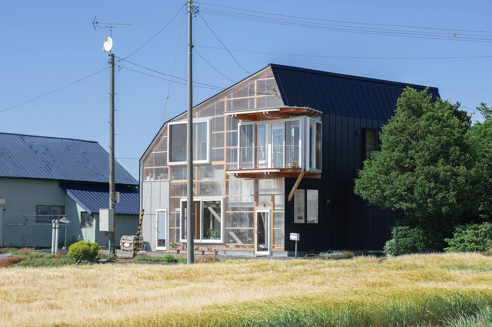 増築した半屋外空間のポリカーボネートと黒色ガルバリウム鋼板のコントラストが目を引く外観