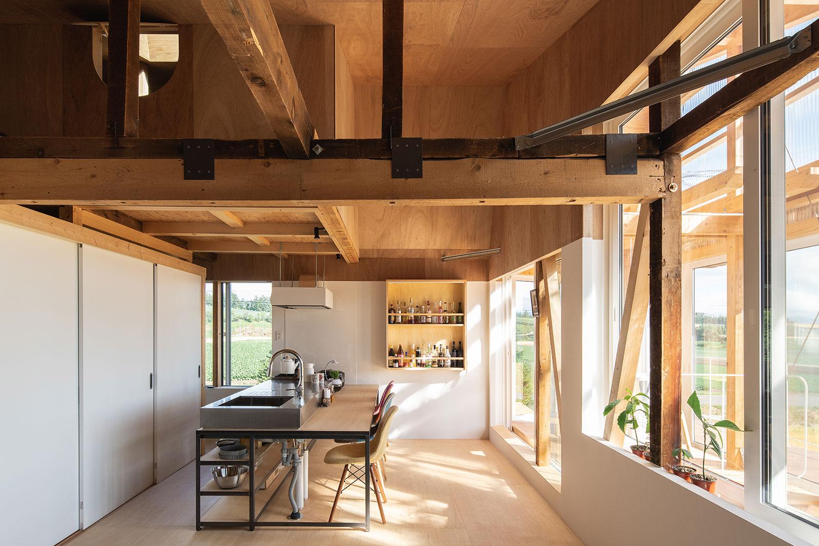 2階子世帯の明るいダイニング・キッチンは構造現しで、屋根なりの高い天井が一層の開放感を与える。床下には、1階の親世帯に配慮して厚手のスタイロフォームを入れ、防音処理を施している
