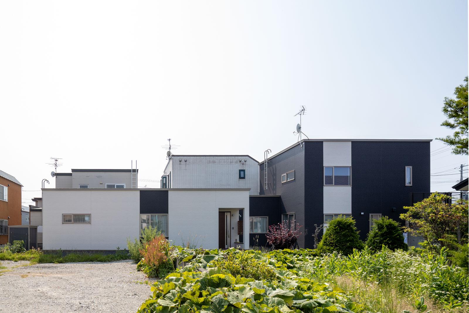左側の平屋が親世帯、右側の2階建てが子世帯の住まい。真ん中のくぼんでいる部分が二世帯をつなぐ通路
