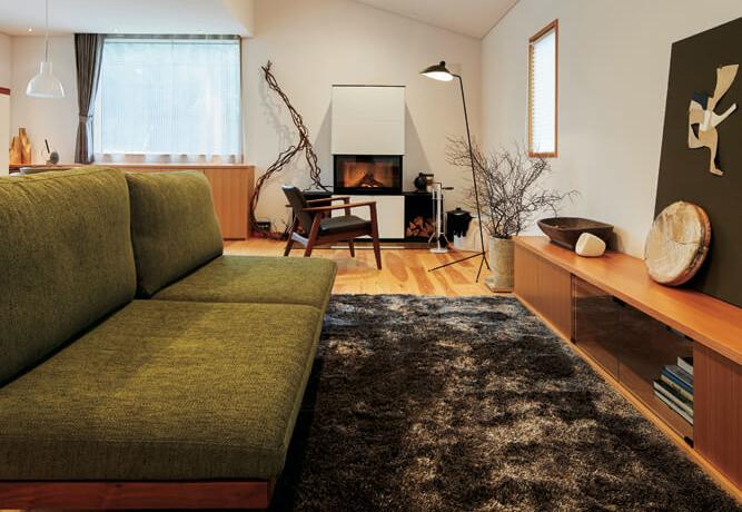 彩度を抑えた若草色のソファが、シンプルな色調でまとめた空間の良いアクセントに。ラグのカーキ色と同系色でコーディネートしているのも効果的
