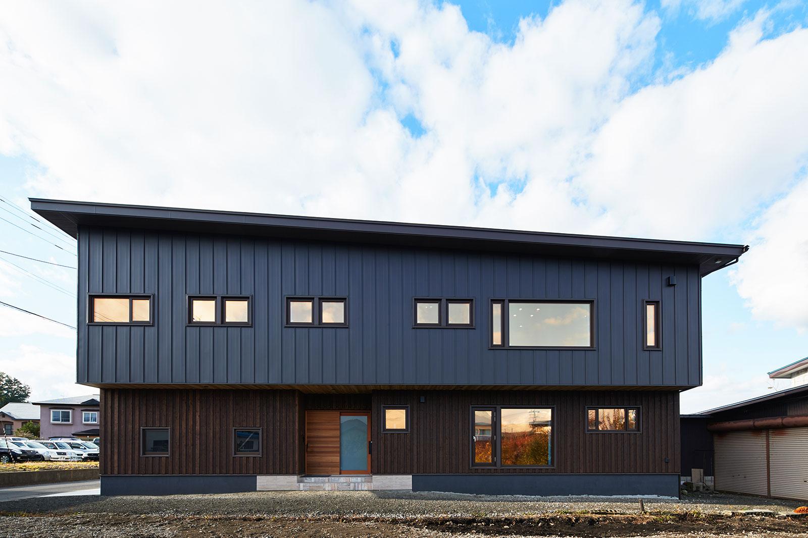 横に長い形状のHさん宅。外観は、2階のガルバリウム鋼板と1階のスギ板張りの対比が美しい