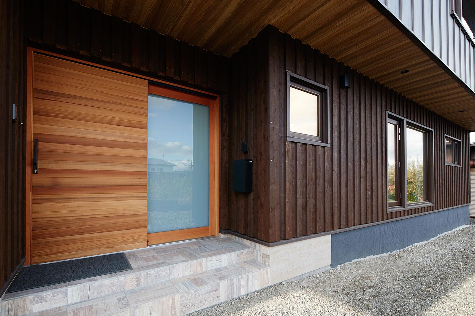 重厚感と木の優しさを兼ね備えた大きな木製引き戸が印象的な共用玄関